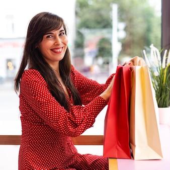 Vista lateral de uma mulher sorridente posando com sacolas de compras