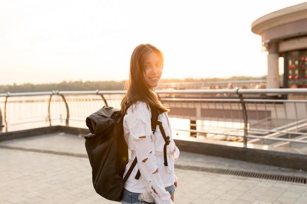 Vista lateral de uma mulher sorridente posando enquanto viaja sozinha