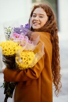 Vista lateral de uma mulher sorridente segurando buquês de flores da primavera