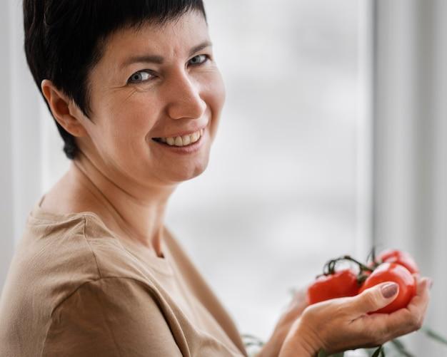 Vista lateral de uma mulher sorridente segurando tomates cultivados em casa
