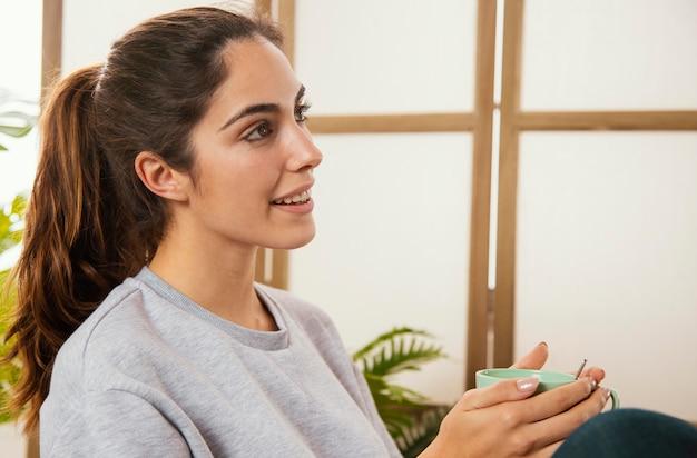 Vista lateral de uma mulher sorridente tomando café em casa