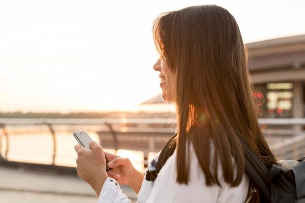 Vista lateral de uma mulher sorridente usando o smartphone enquanto viaja sozinha