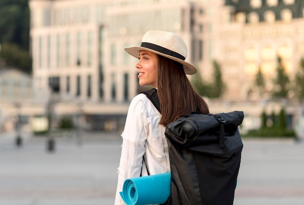 Vista lateral de uma mulher sorridente viajando sozinha com uma mochila