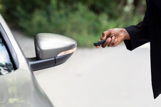 Vista lateral de uma mulher testando as chaves de seu carro novo