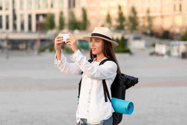 Vista lateral de uma mulher tirando fotos com o smartphone durante uma viagem