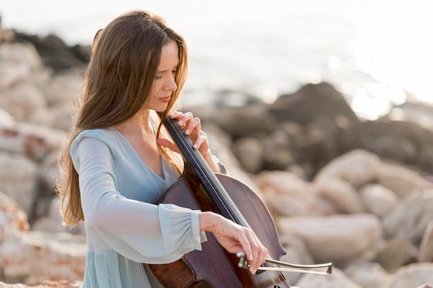 Vista lateral de uma mulher tocando violoncelo nas pedras