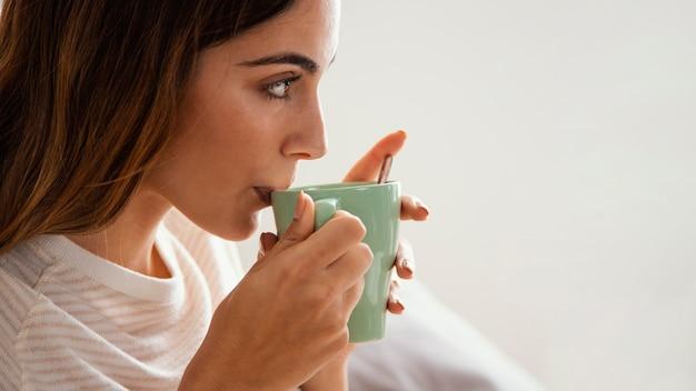 Vista lateral de uma mulher tomando café na cama com espaço de cópia