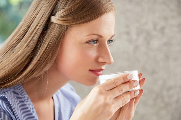 Vista lateral de uma mulher tomando café