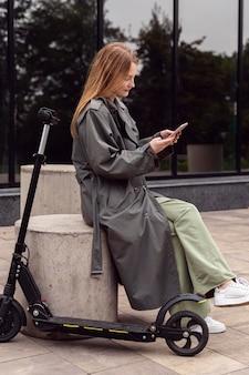 Vista lateral de uma mulher usando seu smartphone ao lado de uma scooter elétrica