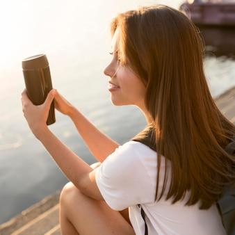 Vista lateral de uma mulher viajando à beira do rio segurando uma garrafa térmica