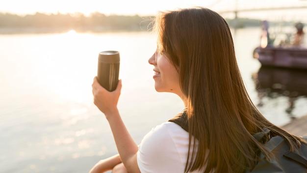 Vista lateral de uma mulher viajando admirando o rio enquanto segura uma garrafa térmica