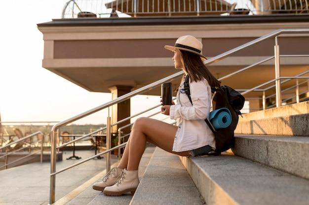 Vista lateral de uma mulher viajando segurando uma garrafa térmica