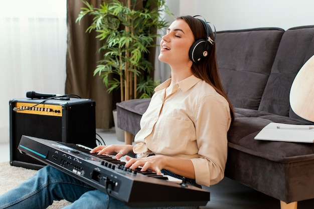 Vista lateral de uma musicista cantando e tocando teclado de piano