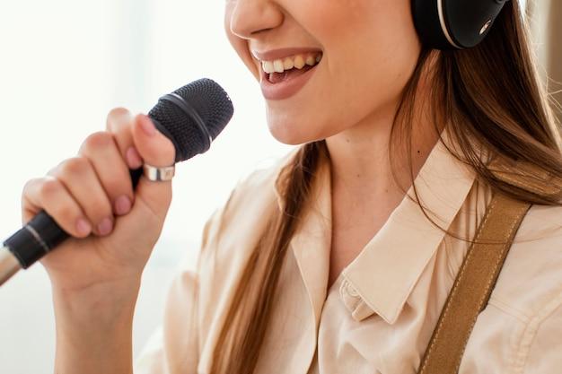 Vista lateral de uma musicista cantando no microfone
