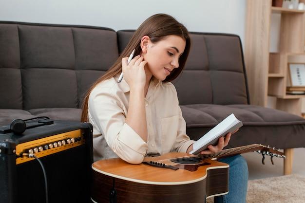 Vista lateral de uma musicista com violão escrevendo canções