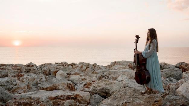 Vista lateral de uma musicista com violoncelo