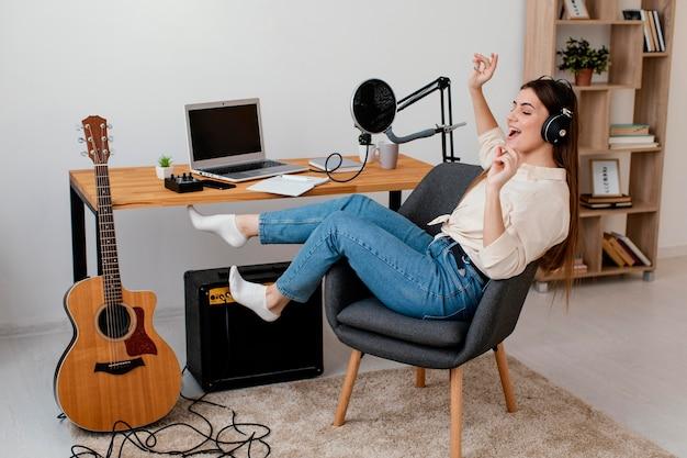Vista lateral de uma musicista em casa cantando com fones de ouvido ao lado de um violão