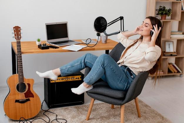 Vista lateral de uma musicista em casa cantando com fones de ouvido