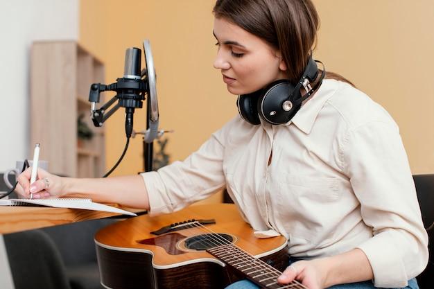 Vista lateral de uma musicista em casa escrevendo músicas enquanto toca violão