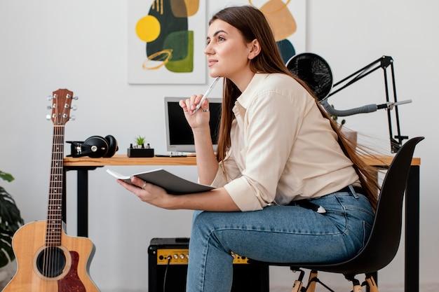 Vista lateral de uma musicista em casa escrevendo músicas
