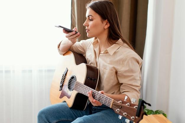 Vista lateral de uma musicista em casa falando para o smartphone enquanto segura o violão
