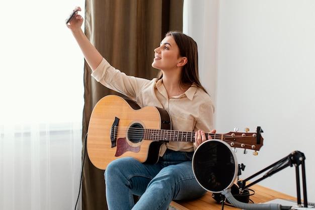 Vista lateral de uma musicista em casa tirando uma selfie enquanto segura o violão