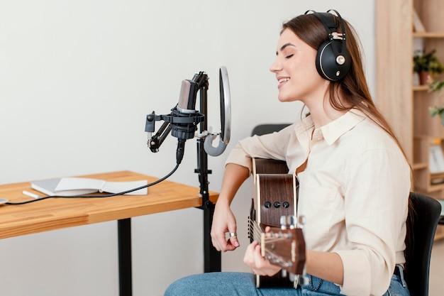 Vista lateral de uma musicista gravando uma música enquanto tocava violão em casa