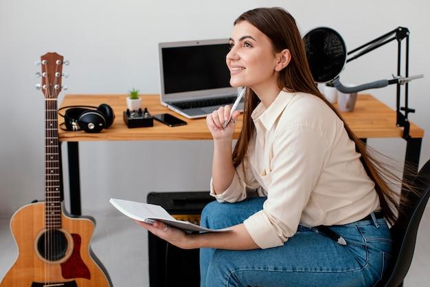 Vista lateral de uma musicista sorridente em casa escrevendo músicas
