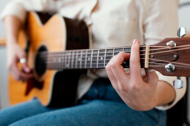 Vista lateral de uma musicista tocando violão