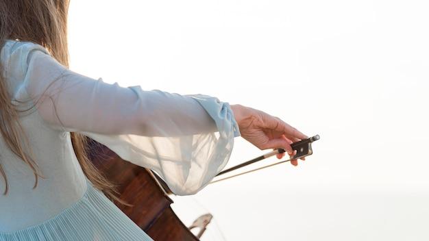 Vista lateral de uma musicista tocando violoncelo com espaço de cópia