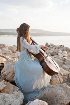 Vista lateral de uma musicista tocando violoncelo nas rochas à beira-mar