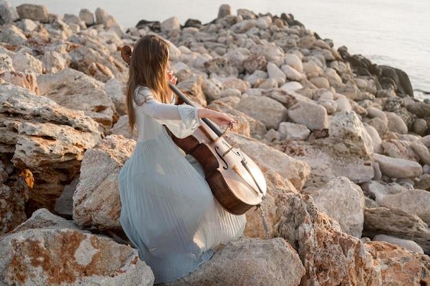 Vista lateral de uma musicista tocando violoncelo sobre pedras