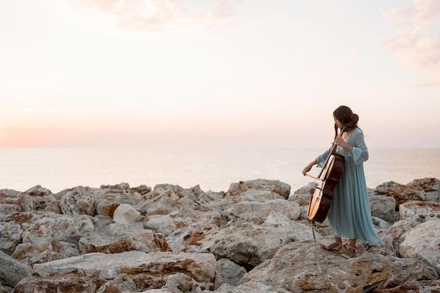Vista lateral de uma musicista tocando violoncelo