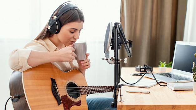 Vista lateral de uma musicista tomando um drinque enquanto toca violão em casa