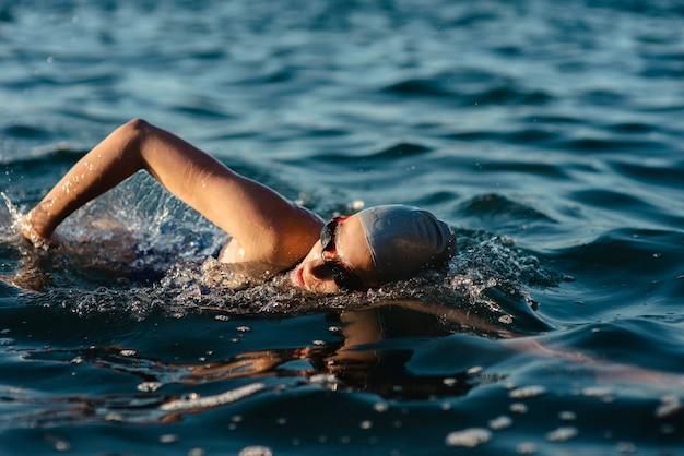 Vista lateral de uma nadadora com boné e óculos de proteção nadando na água