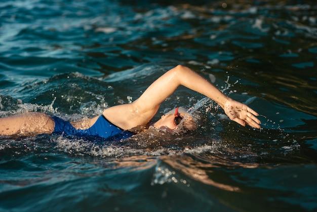 Vista lateral de uma nadadora nadando na água