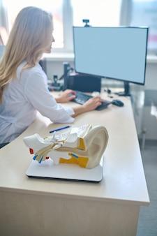 Vista lateral de uma otorrinolaringologista profissional vestindo um jaleco, sentada à mesa de uma clínica de audição