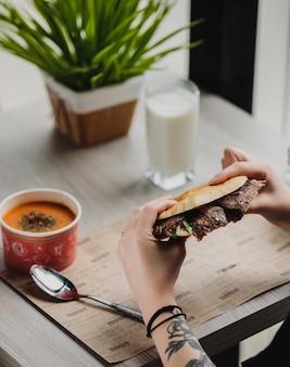 Vista lateral de uma pessoa que come doner kebab em pão pita à mesa
