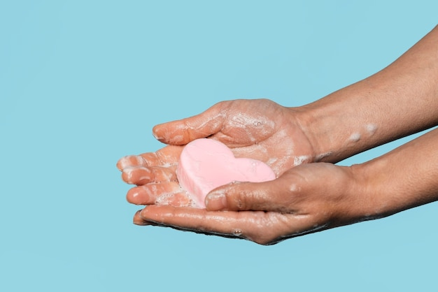 Vista lateral de uma pessoa segurando um sabonete em forma de coração
