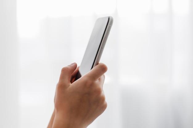 Vista lateral de uma pessoa segurando um telefone celular