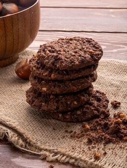 Vista lateral de uma pilha de biscoitos de chocolate com nozes cereais e cacau na madeira