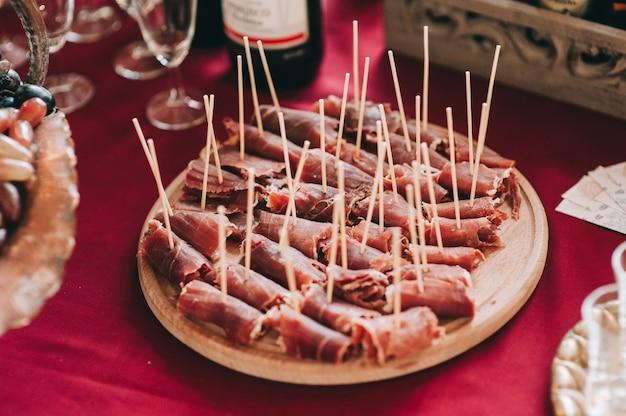 Vista lateral de uma placa de madeira redonda com pedaços de carne fatiada e torcida em espetos. refeições.