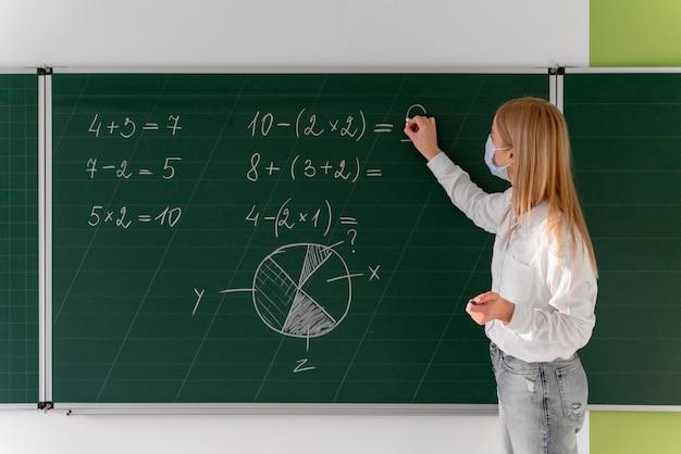 Vista lateral de uma professora com máscara médica ensinando em sala de aula usando o quadro-negro
