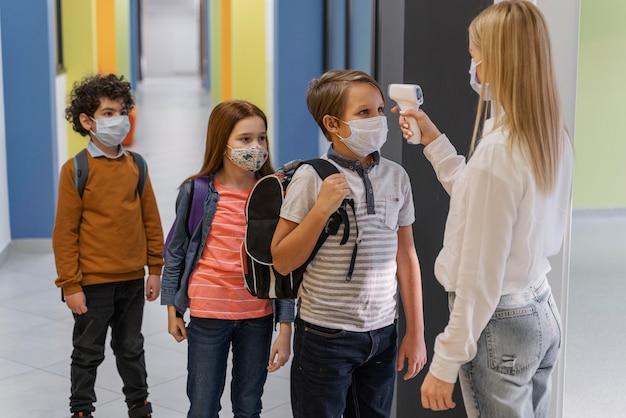 Vista lateral de uma professora com máscara médica, verificando a temperatura das crianças na escola