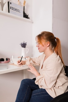 Vista lateral de uma professora em casa escrevendo a agenda durante a aula online