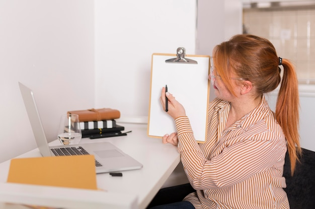 Vista lateral de uma professora mostrando a aula online