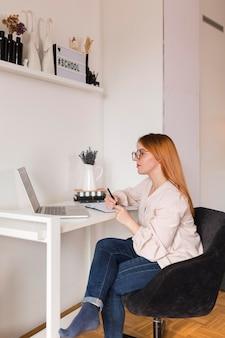 Vista lateral de uma professora na mesa durante a aula online
