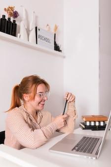 Vista lateral de uma professora sorridente usando um laptop durante a aula online