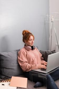 Vista lateral de uma professora usando laptop em casa para dar uma aula online