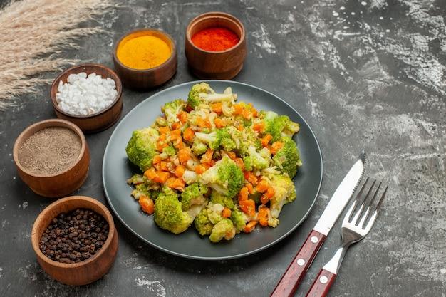 Vista lateral de uma refeição saudável com brocoli e cenoura em uma placa preta e especiarias na mesa cinza
